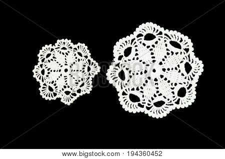 Two white crocheted coasters on the black background. Not isolated. Lace doily.