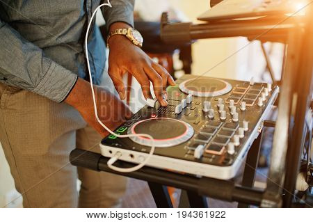 African American Dj In Huge White Headphones Creating Music On Mixing Panel.