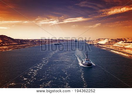 Evening atmosphere in the Suez Canal - a ship convoy passes through the new eastern extension canal opened in August 2015