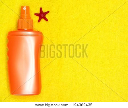 Bottle of sunscreen spray with small starfish on terry towel. Copy space