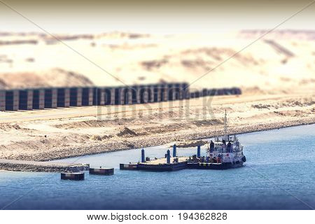 Construction work with work ship in the new extension channel of the Suez Canal in the background lots of sand masses and containers low depth of field