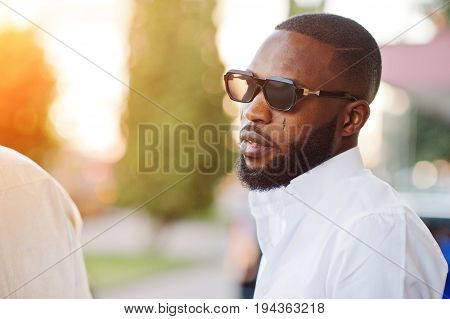 Black Men Stylishly Clothed Standing And Talking Outside On The Street In The Downtown.