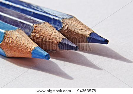 Blue pencils on white background, closeup and macro photography