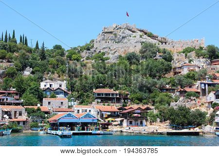 Kekova, Turkey- 2 Jun 2017: Coast of the island in the Mediterranean sea, modern picturesque village with the ruins of ancient Lycian towns and tombs-sarcophagi of Aperlai, Simena Teimussa Dolihiste.