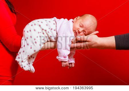 Family parenthood artistic concept. Baby lying and sleeping on mother and father arms. Red background.