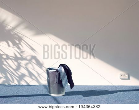 Suit in waste bin on carpeted floor against white wall