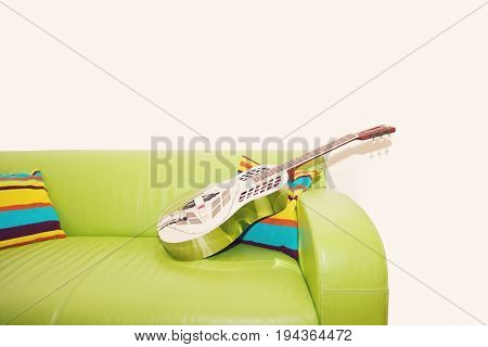 Resonator Guitar on a Green Sofa
