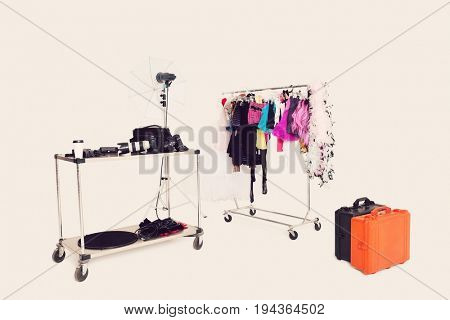 Clothes rack and photographic equipments with suitcases in studio