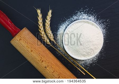 Wheat flour in white cup and organic egg decorate by wheat ear, rolling pin on black slate stone plate with copy space for preparing baking or pasta