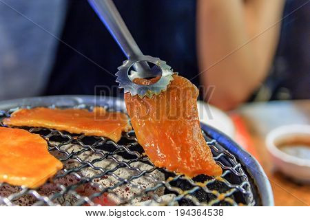 Grilling Raw Sliced Pork over Hot Charcoal Stove Japanese Barbecue Style called Yakiniku Selective focus