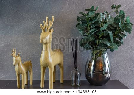 home interior decoration: Wood carving deer and vases with aromatic bamboo sticks perfume diffuser and freshener in bathroom on brown wooden shelves