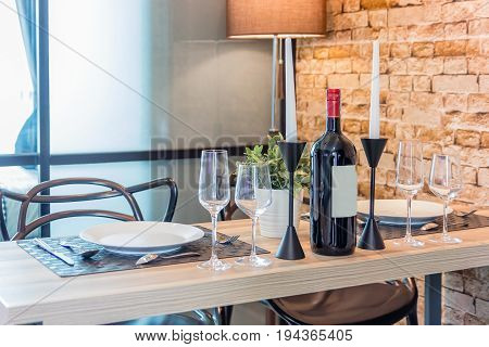 White empty plate with knife glasses forks knives and plates on a table in restaurant served for dinner