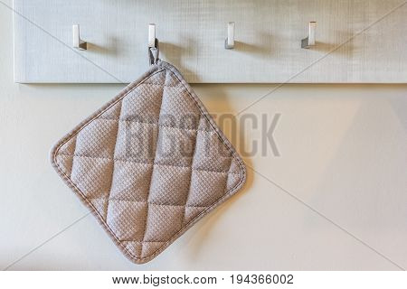 brown squared kitchen towel hanging on wooden wall background