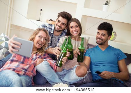 Group of attractive young people sitting on the sofa doing selfie and smiling.