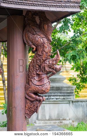 Wooden statue of King of Naga (Serpent King) on wooden poll of temple in Thailand.