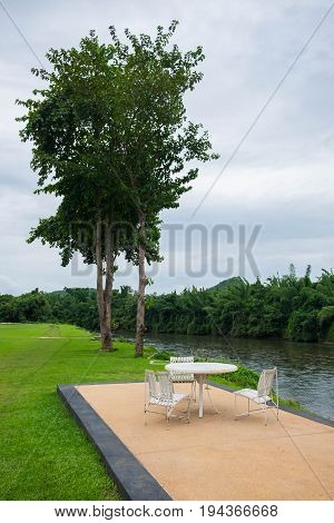Relaxation area with old white wooden table and chair in garden by the river.