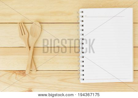 Closed up wooden spoon fork and lined paper on wooden table top view