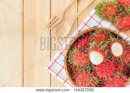 fresh tropical rambutan fruits over basket with spoon and fork on wood background Top view with copy space and text.