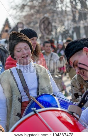 PERNIK, BULGARIA - JANUARY 27, 2017: Young boy, a drummer is smiling while participating in a drum show to make more noise and chase away the evil spirits at Surva, the International Festival of the Masquerade Games