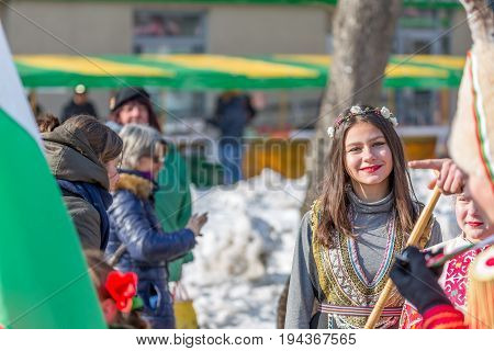 PERNIK, BULGARIA - JANUARY 27, 2017: Young woman is smiling and looking at the camera wearing a traditional female folklore costume at Surva, the International Festival of the Masquerade Games