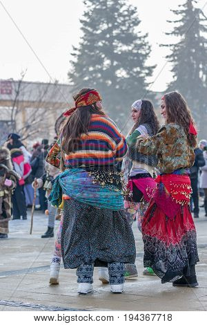 PERNIK, BULGARIA - JANUARY 27, 2017: Few young women dressed in colorfoul clothes are pretending to be gipsies at Surva, the International Festival of the Masquerade Games