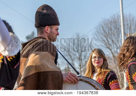 PERNIK, BULGARIA - JANUARY 27, 2017: Young lady with beautiful haircut and glasses is wearing a typical folklore costume, posing and smiling at Surva, the International Festival of the Masquerade Games