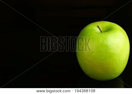 Granny Smith apple on a black background.