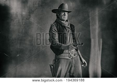 Old Worn Wet Plate Photo Of Vintage Western Actor. Shooting With Revolver.