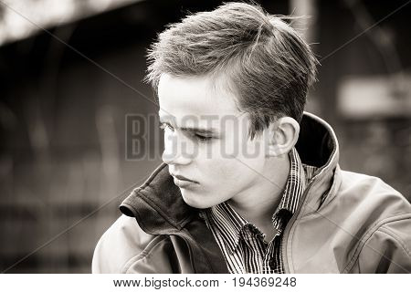 Black And White Image Of Frowning Boy In Jacket