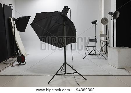 Professional photographic studio set with flashlights and white background. Equipment