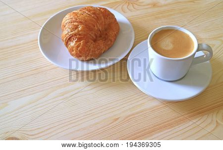 One Butter Croissant and a Cup of Hot Coffee Served on Wooden Table, with Free Space Space for Text and Design