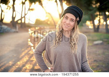A female model wearing a beanie during golden hour. Winter/Fall Themed