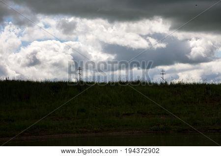 Orthodox Cross In High Green Grass On A Background Gloomy Sky
