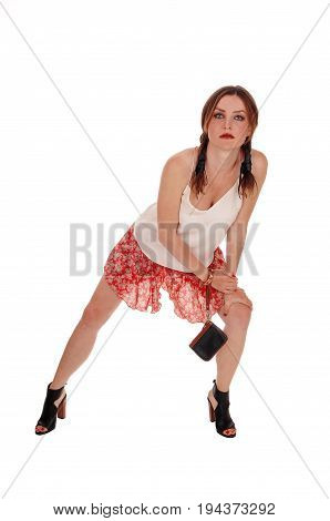 A gorgeous young woman bending forwards is shorts and high heels looking serious isolated for white background.