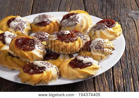 Shortbread cookie with jam and sugar icing in plate on old wooden table