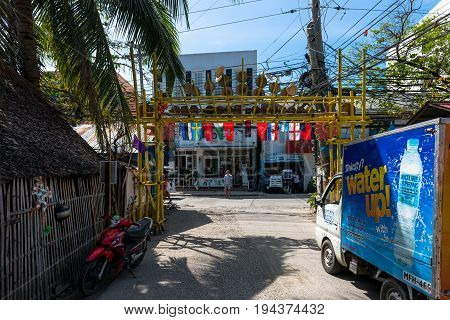 BORACAY, WESTERN VISAYAS, PHILIPPINES - JANUARY 11, 2015: Street on Boracay Island with a motocycle small truck and a way with different flags.