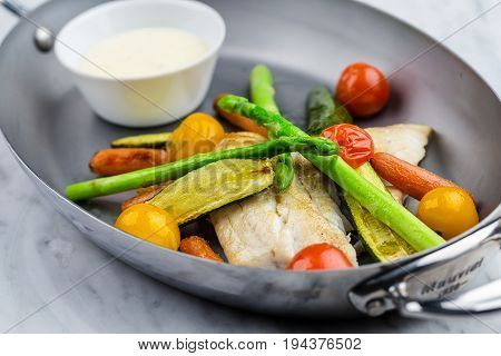 Grilled fish and vegetables with sauce served in metalic bowl on marble serface