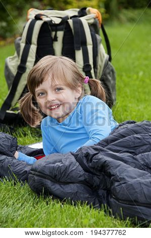 little girl camping laying on a sleaping bag