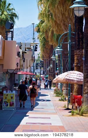 July 3, 2017 in Palm Springs, CA:  People walking in Downtown Palm Springs, CA beside retail shops, restaurants, and Palm Trees and where tourists can experience shopping and dining in a desert ambiance