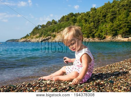 Baby girl 1 year 3 months on a sea beach plays with pebbles