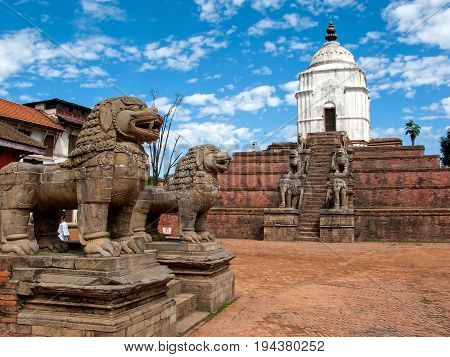 KATHMANDU, BHAKTAPUR, NEPAL: Ancient stone lions and the large white Fasidega Temple dedicated to Shiva in the Durbar Square in Bhaktapur, Kathmandu valley