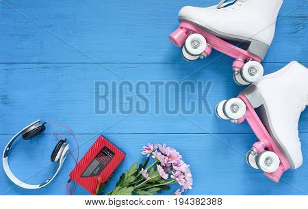 Sport, healthy lifestyle, roller skating background. White roller skates, headphones and vintage tape player. Flat lay, top view.