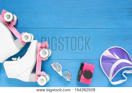 Sport, healthy lifestyle, roller skating background. White roller skates, sunglasses, pink visor hat and vintage camera. Flat lay, top view.