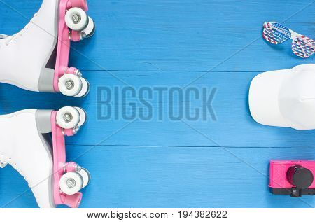 Sport, healthy lifestyle, roller skating background. White roller skates, sunglasses, white baseball cap, vintage pink camera. Flat lay, top view.