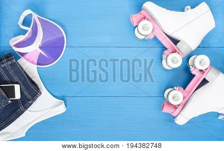 Sport, healthy lifestyle, roller skating background. White roller skates, clothing set, cell phone and pink visor hat. Flat lay, top view.