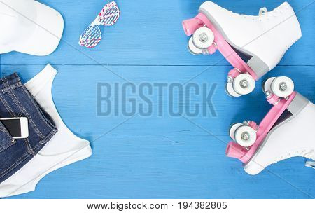 Sport, healthy lifestyle, roller skating background. White roller skates, girl clothing set, cell phone, sunglasses and white baseball cap. Flat lay, top view.
