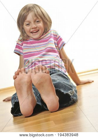 smilling little girl sitting on a wooden floor