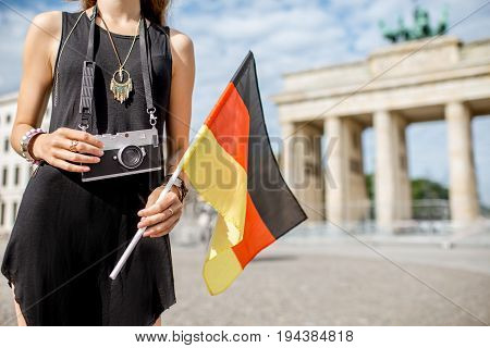 Young woman tourist holding a photo camera and german flag standing in front of the famous Brandenburg gates in Berlin