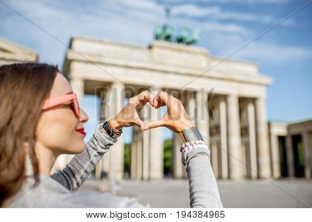 Young woman tourist making heart shape with hands in front of the famous Brandenburg gates in Berlin