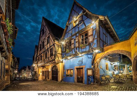 Colorful traditional half-timbered french houses on central street of Riquewihr village in the evening Alsace France